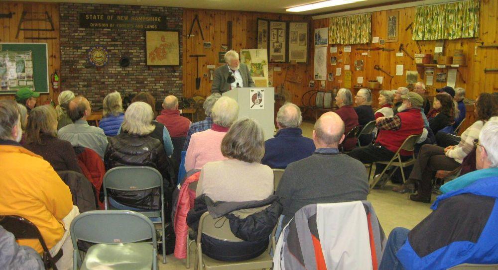 Audience members watch as speaker Steve Taylor speaks at a wooden podium.