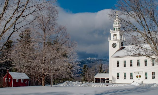 A spectacular view of Mount Monadnock is seen from in between a church and barn.