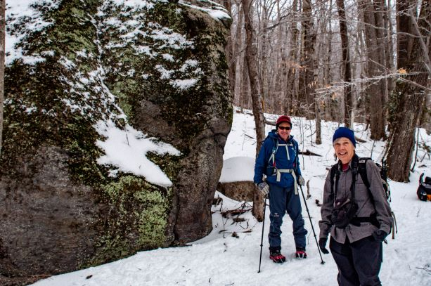 Two hikers pause by a large boulder covered in lichen and snow.