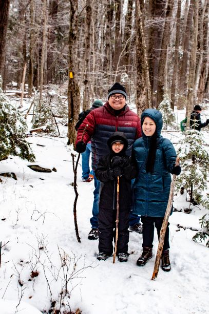 A family poses together on a snowy trail.