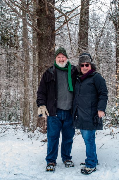 A couple poses together on the snowy trail.