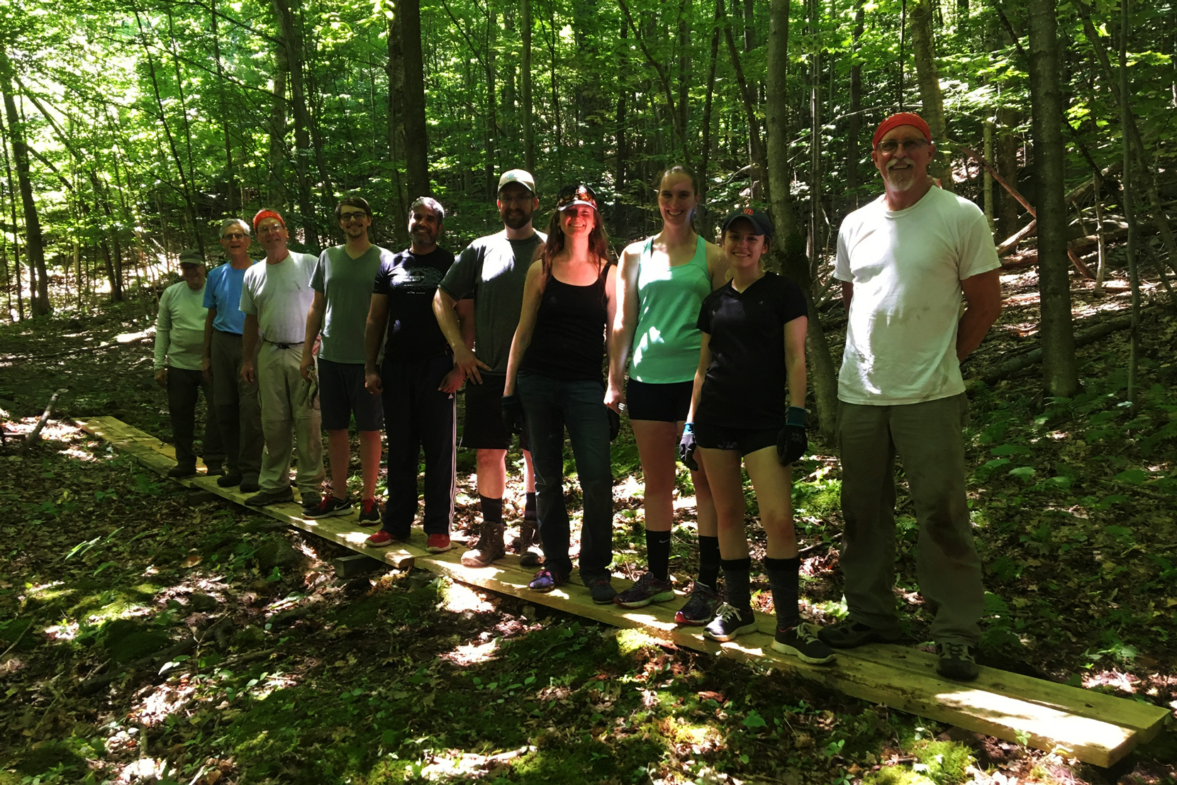 Volunteers showcase a completed bog bridge on the XC Ski Trail