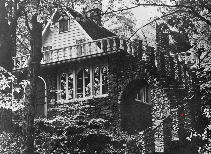 A black and white photo of Madame Sherri's original house with a winding outdoor stone staircase.