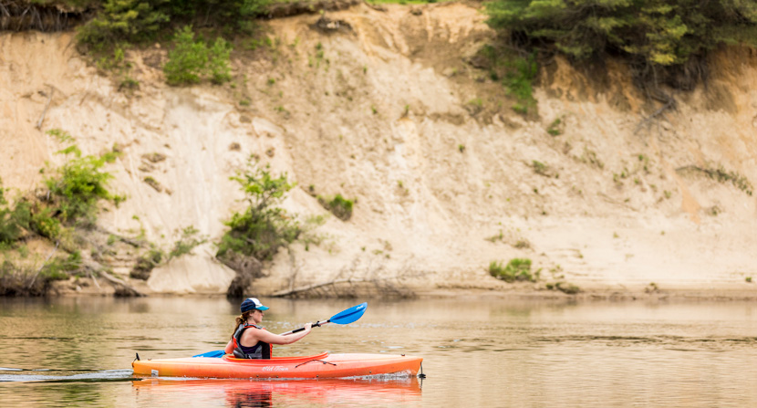 A kayaker paddles alongside Stillhouse Forest in Canterbury, New Hampshire
