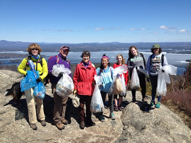 A group of hikes poses at the summit of Mt Major with the trash they collected.