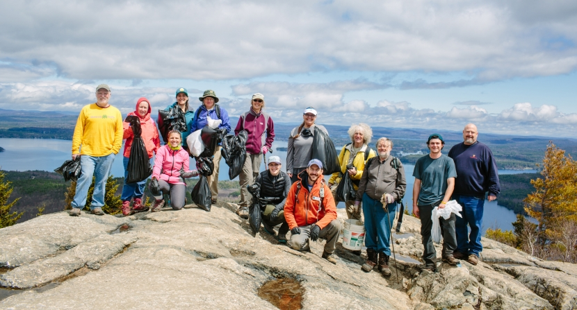 Volunteers take a break to pose for a photo on the summit of Mount Major.