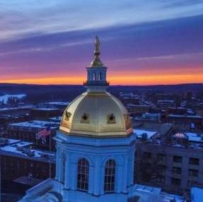 NH State Capital dome against sunrise sky