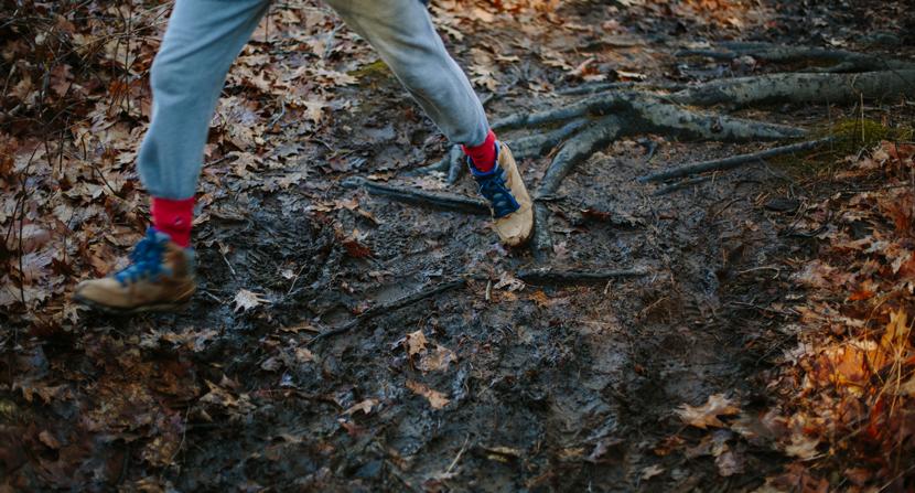 Boy hiking and running along muddy trail