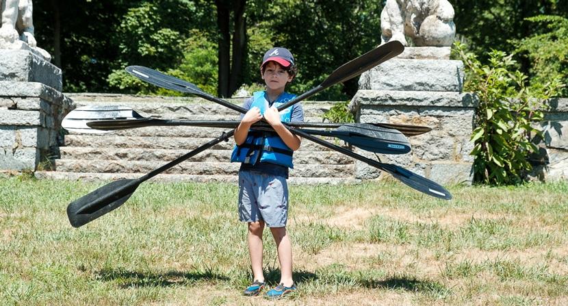 Kid carrying oars at Gundalow River Rats camp environmental and outdoor education