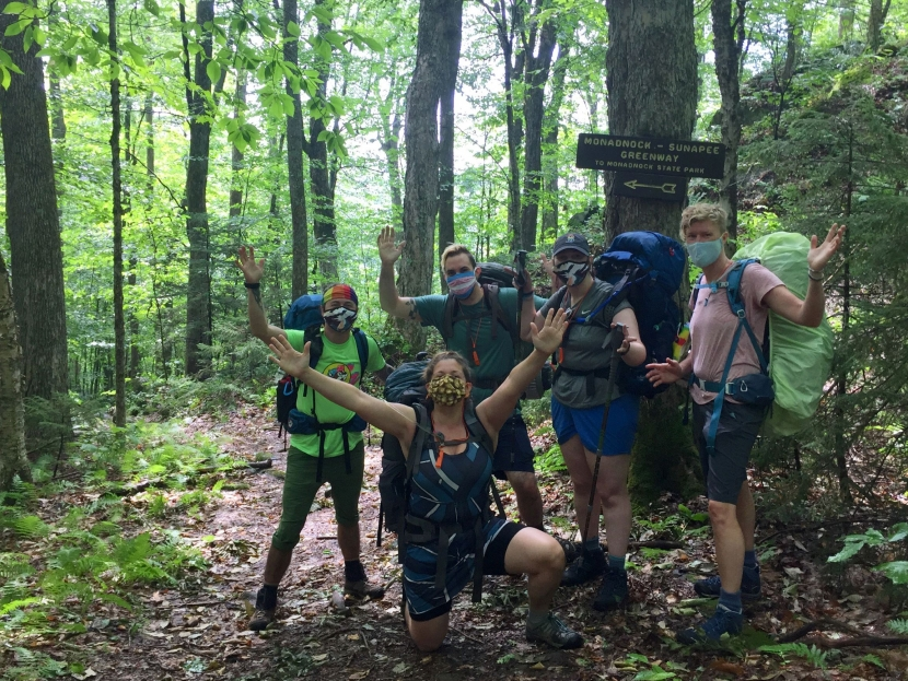 A group of masked hikers poses in front of a sign on the Monadnock-Sunapee Greenway trail.