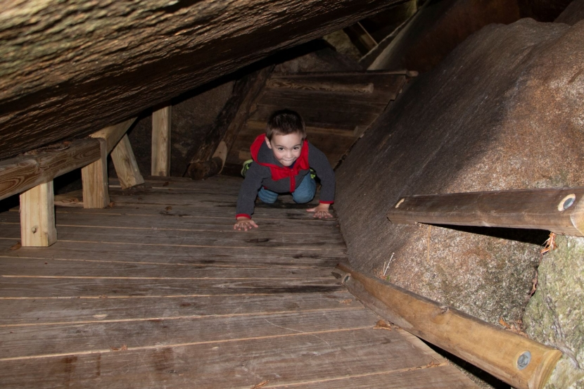 A preschool boy bear crawls through a dark cave.