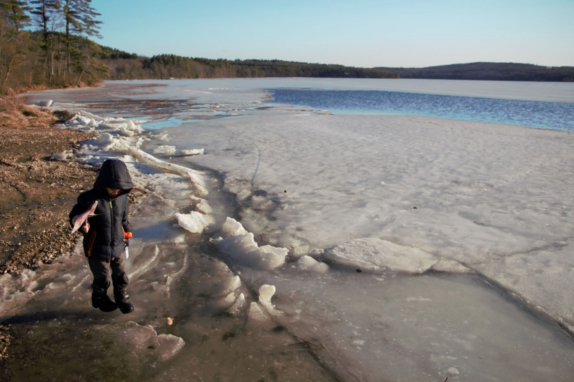 A boy in snow boots stands near an icy lake holding a pinwheel.