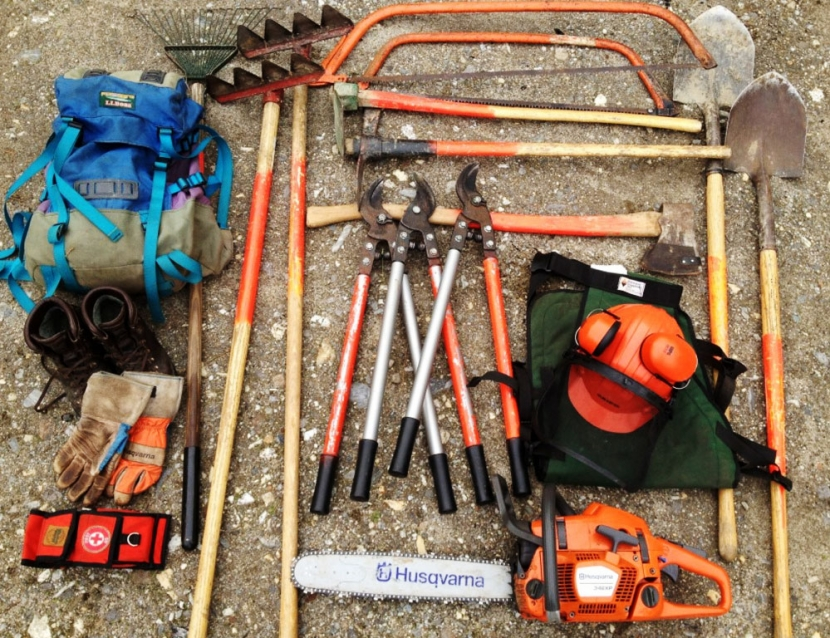 Forestry tools including gloves and a timber jack are organized on the ground.