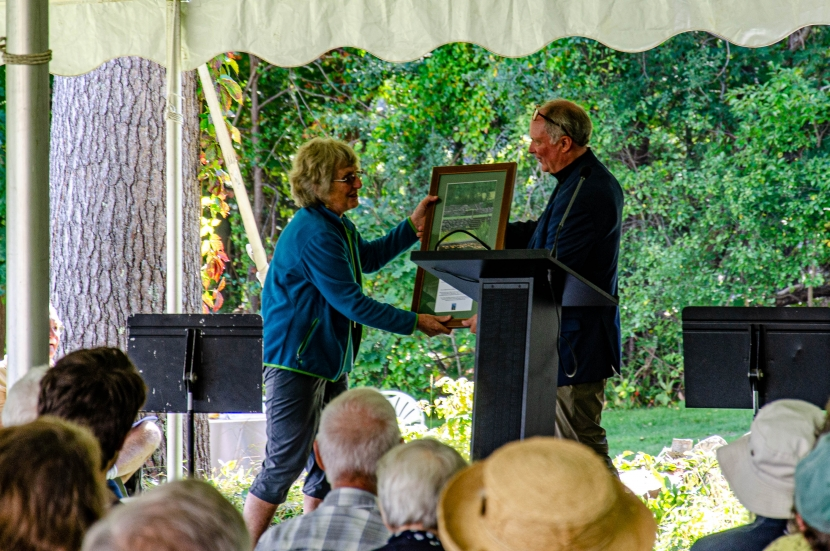 Volunteer of the Year Janet Hill accepts a plaque on stage from President Jack Savage.