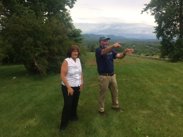 Congresswoman Kuster and SPNHF President Jack Savage standing in front of misty view of the White Mountains at The Rocks in Bethlehem.