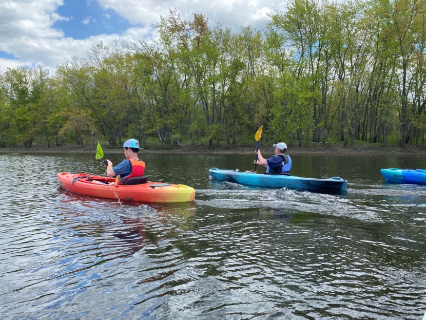 A father and son, both in lifejackets, kayak together on the Merrimack River.