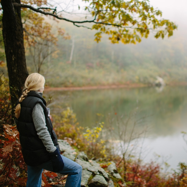 Hiker looks out on a foggy pond in autumn