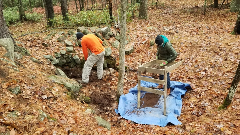 Two archaeologists look down into a cellar hole at Monson Center.