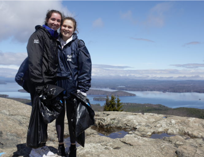 standing on mount major with trash bags of collected litter