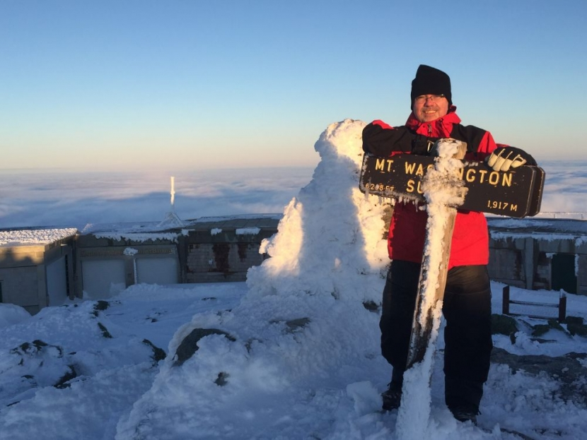 Dan Szczesny in red parka poses at rime ice crusted summit sign on Mt Washington in winter