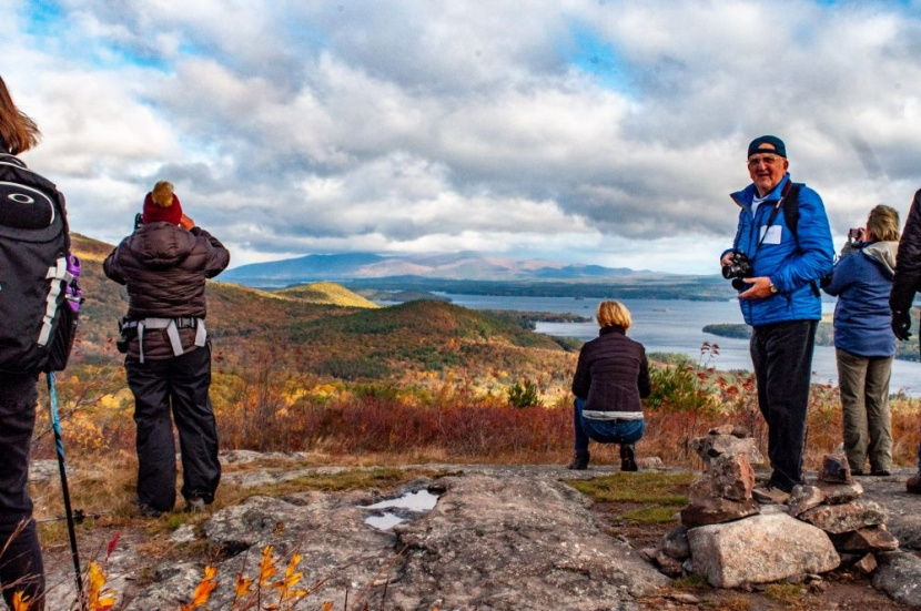 Hikers enjoying autumn view of Lake Winnipesaukee and Belknap Range from summit of Pine Mountain on Forest Society Morse Preserve