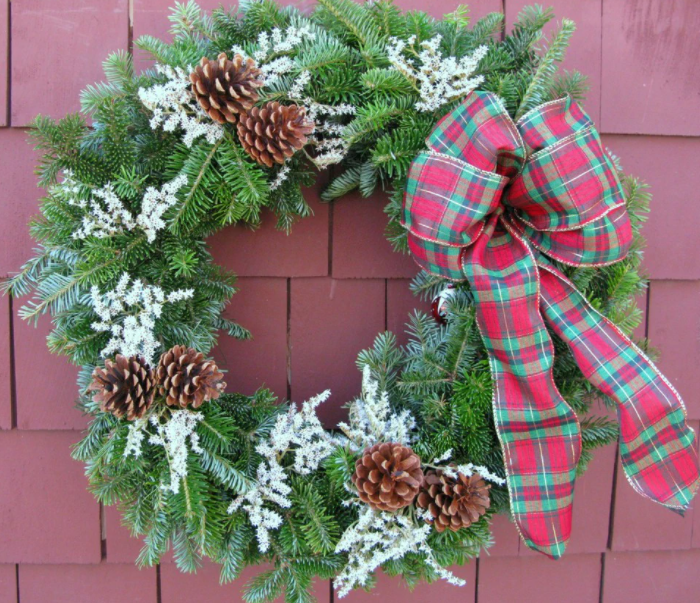 A Christmas wreath hangs on a red barn wall.