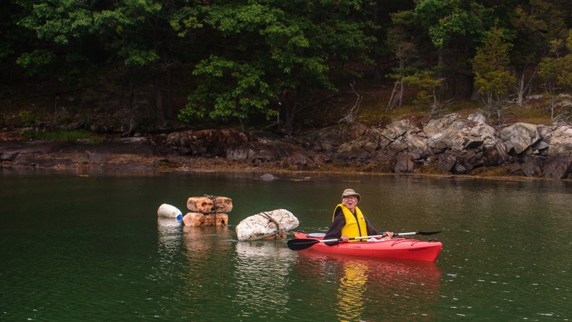 Volunteer comes up with creative way to tow trash in a kayak