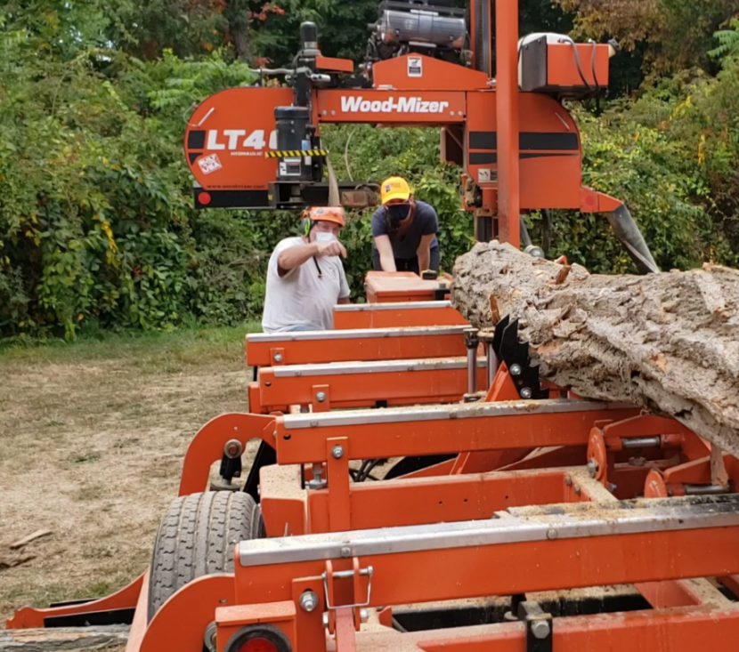 A forester in a hard hat demonstrates a large portable saw mill to a visitor in a hard hat.