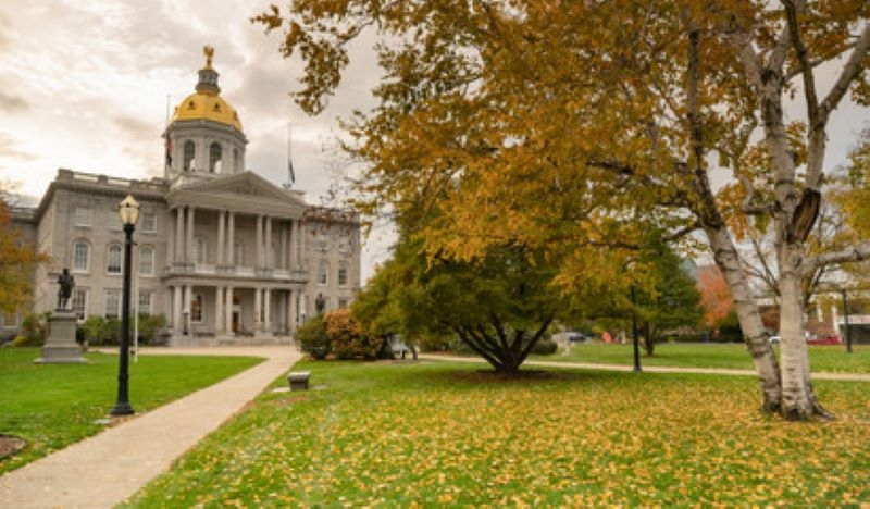 NH State House with fall leaves and colors blue sky