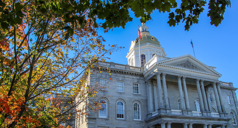 New Hampshire State House surrounded by trees and fall foliage in autumn