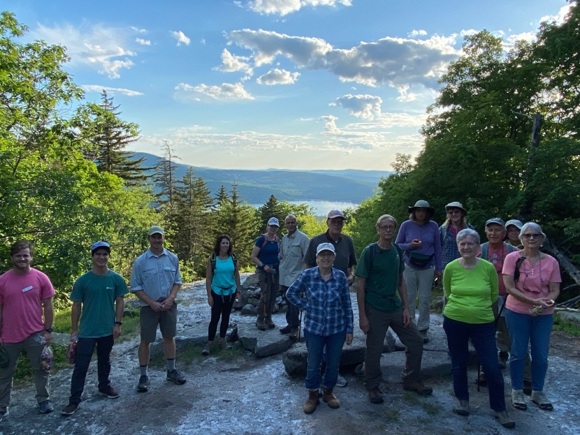 Colorful T-shirts of hikers in shadow at summit of Sunset HIll, view of Lake Sunapee in background