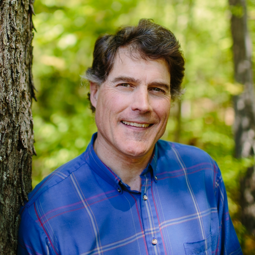 Tom Howe poses in the forest outside of the Conservation Center.