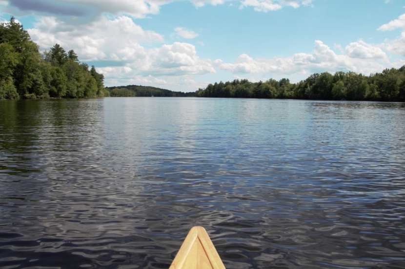 The bow of a canoe with the Merrimack River ahead.