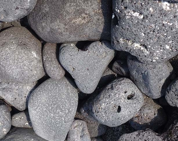 A heart-shaped rock sits in the middle of a rock pile.