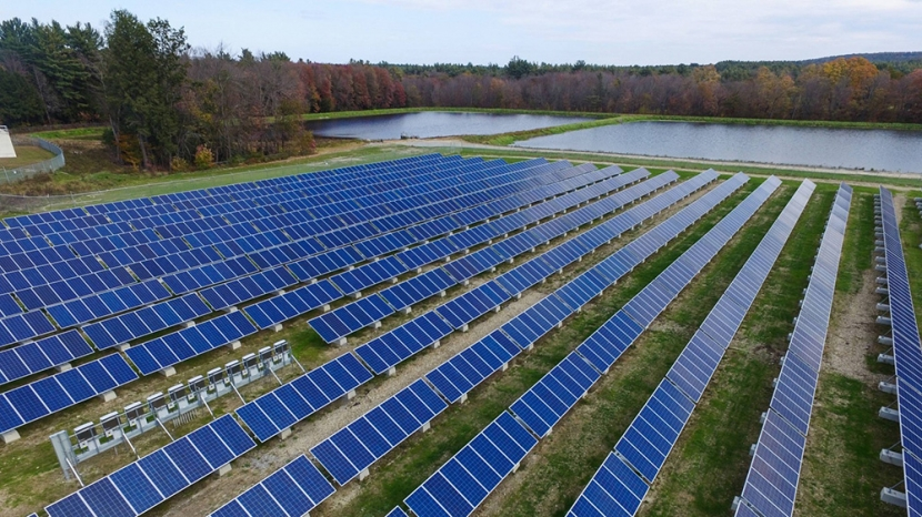 three large fields of solar panels surrounded by forest