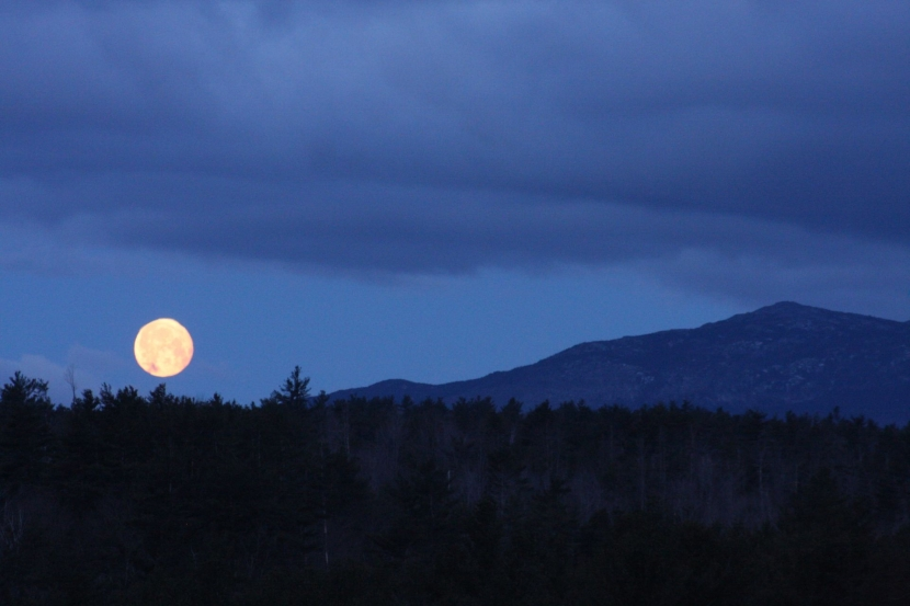A moon rises over the mountain.