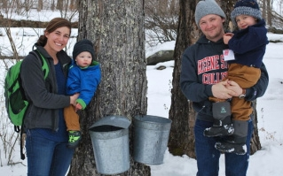 A family poses by a maple bucket during the NH Maple Experience.