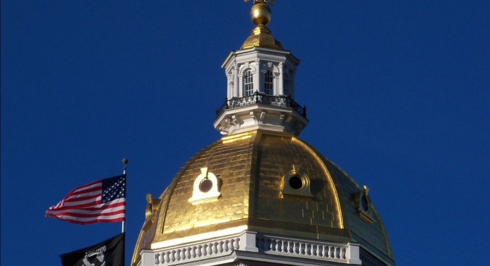 NH State Capital Dome against blue sky, American and POW flag waving