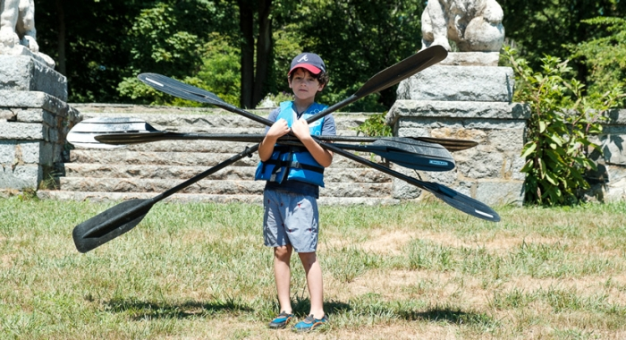 Kid carrying oars at Gundalow River Rats camp environmental and outdoor education