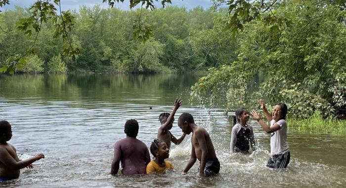 Kids splash in the Merrimack River on a hot day.