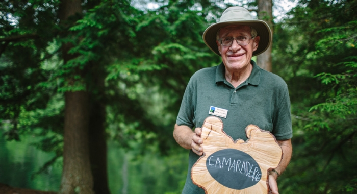 """Camaraderie"" sums up this land steward's volunteer experience. Written on a rustic tree cookie chaulkboard."