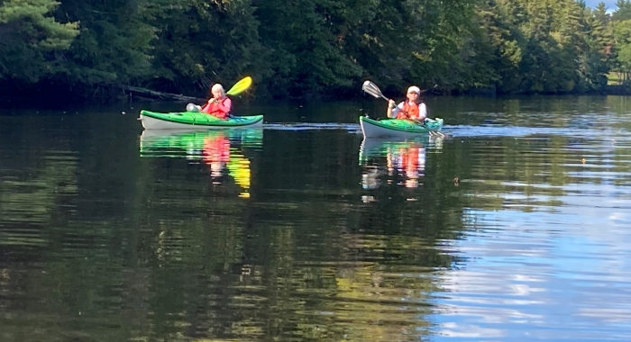Kayakers paddle on the Contoocook River.
