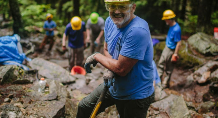 Trail volunteer poses with sledgehammer, eye protection, and a hardhat
