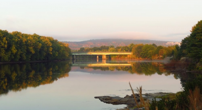View looking west upriver at I-93 bridge over Merrimack River in soft, pink morning light on wide, placid river in Concord, NH