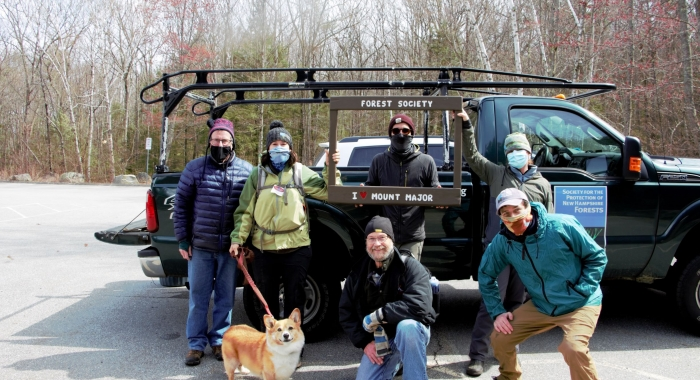 Forest Society staff and volunteers pose in the parking lot at Mt Major with a truck full of collected trash behind them.