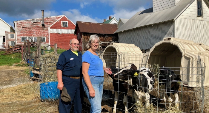 The Morrills stand next to a cow in front of a red barn.