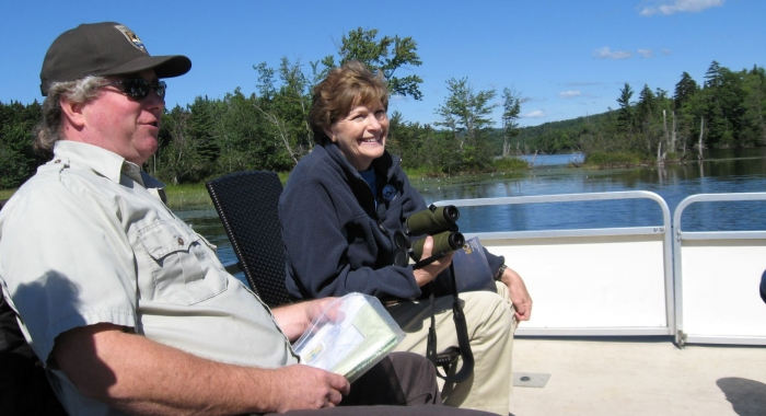 Senator Jeanne Shaheen smiling with binoculars sitting on boat with USFW Staff on Lake Umbagog on a clear blue sky day.