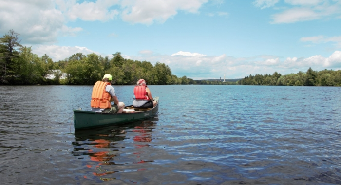 Two people in lifejackets in a canoe on the Merrimack River as seen from behind.
