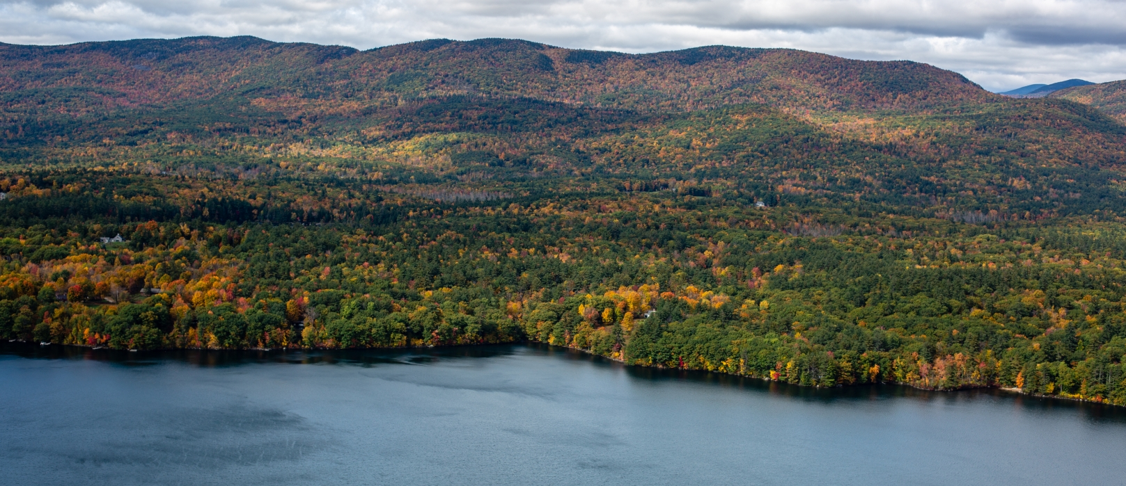 A view from Eagle Cliff of autumn foliage among hills and mountains in the distance.
