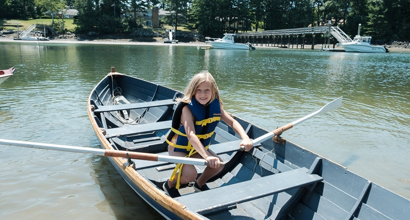 Camper rows a boat on Sagamore Creek for Gundalow Company outdoor camps